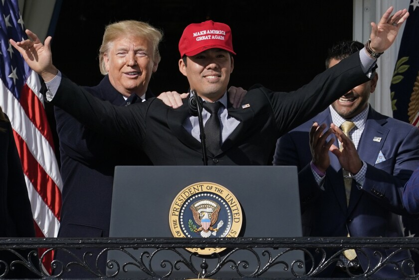 "Washington Nationals catcher Kurt Suzuki wears a ""Make America Great Again"" hat as he is embraced by President Trump, with Nationals manager Davey Martinez looking on."