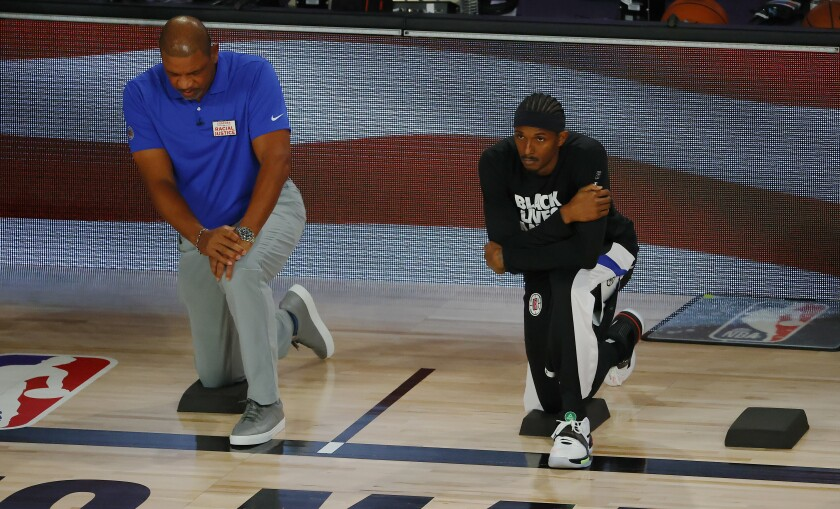 Clippers' Lou Williams, right, and coach Doc Rivers take a knee during the national anthem.