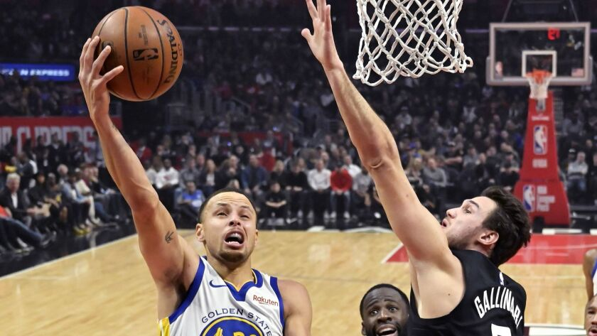 Warriors guard Stephen Curry, left, drives for a layup as Clippers forward Danilo Gallinari defends during the first half of a game on Jan. 18, 2019, in Los Angeles.