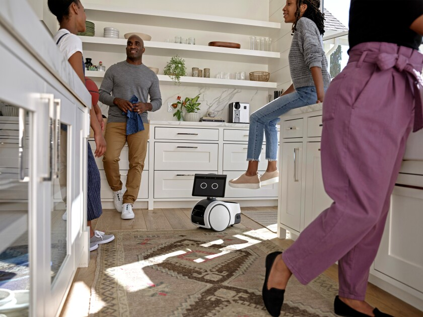 People hanging out in a kitchen with Amazon's robot, Astro, on the floor.
