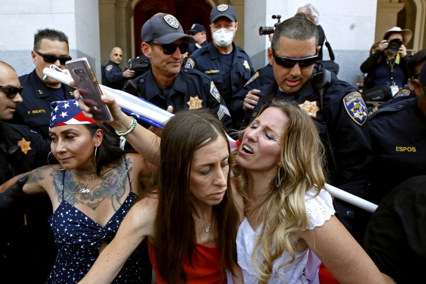 Freedom Angels co-founders, from left, Denise Aguilar, Heidi Muñoz Gleisner and Tara Thornton as they are detained by California Highway Patrol officers during a demonstration against Gov. Gavin Newsom's stay-at-home orders aimed at slowing the spread of the new coronavirus, at the Capitol in Sacramento on May 1.