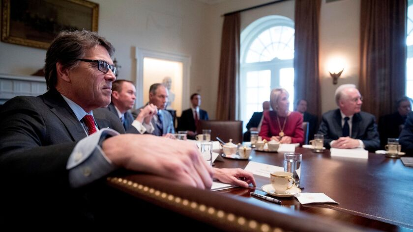 Energy Secretary Rick Perry, left, listens as President Donald Trump speaks during meeting in the Cabinet Room of the White House in Washington on March 13.