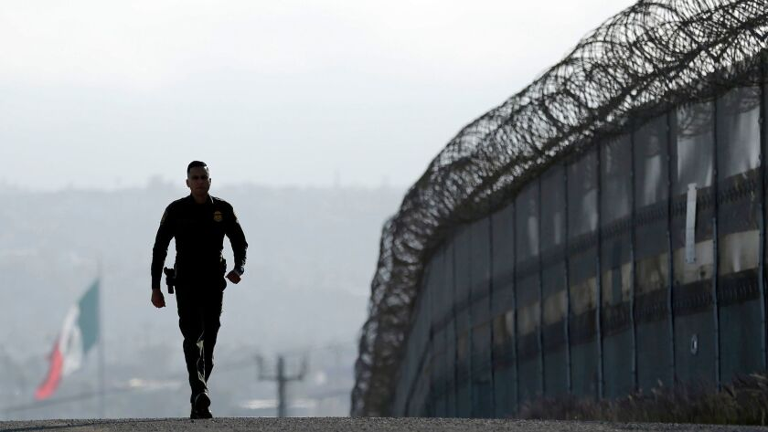 Border Patrol agent Eduardo Olmos walks near the secondary fence separating Tijuana, Mexico, from San Diego in 2016.