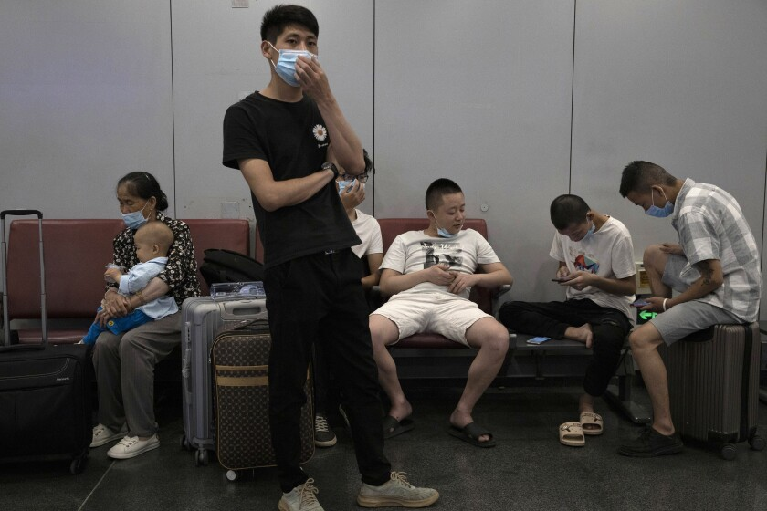 Passengers wait for their flight at the Beijing Capital Airport terminal 2 in Beijing on Wednesday, June 17, 2020. The Chinese capital on Wednesday canceled more than 60% of commercial flights and raised the alert level amid a new coronavirus outbreak, state-run media reported. (AP Photo/Ng Han Guan)