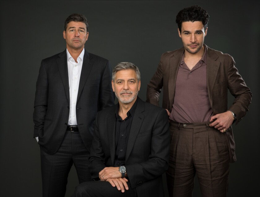 "George Clooney, center, with actors Kyle Chandler, left, and Chris Abbott, stars in and directs an adaptation of Joseph Heller's satirical novel ""Catch 22"" for Hulu. They posed for this portrait at New York's Carlyle Hotel on May 1, 2019."
