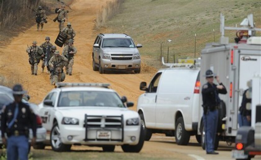 """FILE - In this Jan. 30, 2013 file photo, heavily armed men move away from the home of Jimmy Lee Dykes in Midland City, Ala., where he is holding a 5-year-old boy hostage after kidnapping him from a school bus the day before. The boy's mother told Dr. Phil McGraw in an interview to be aired on the """""""