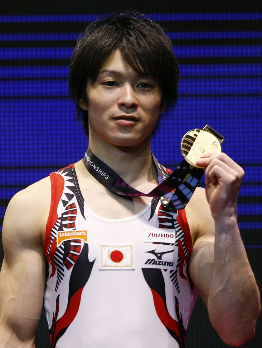 Winner Japan's Kohei Uchimura poses with his gold medal after his horizontal bar exercise during the men's apparatus final competition at the World Artistic Gymnastics championships at the SSE Hydro Arena in Glasgow, Scotland, Sunday, Nov. 1, 2015. (AP Photo/Matthias Schrader)