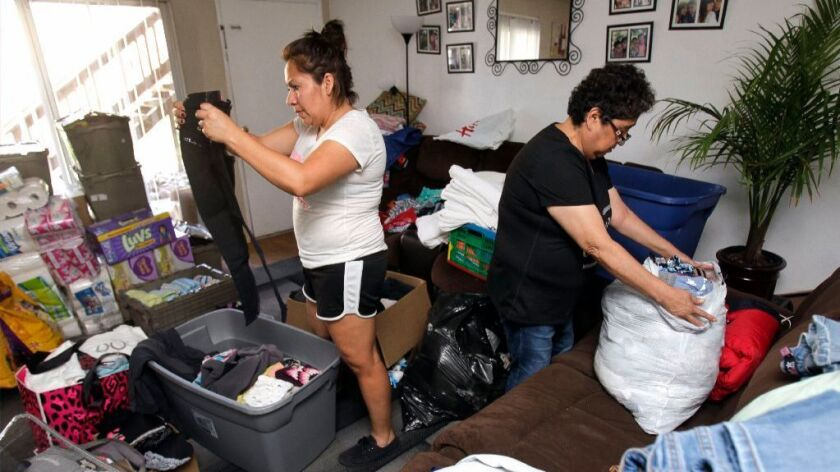 Maria Hernandez, left, and her mother-in-law Trinidad Fletes sort through clothing and other items f