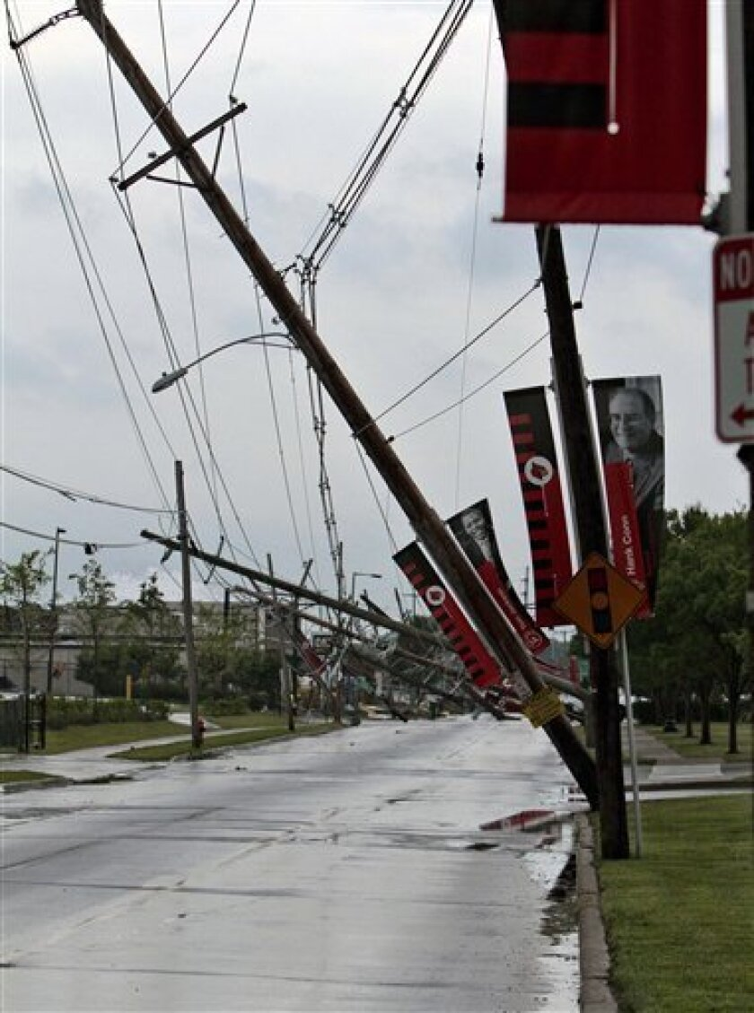 Numerous power poles snapped near their base along Floyd Street and Central Avenue outside Cardinal Stadium at the University of Louisville in Louisville, Ky., Wednesday, June 22, 2011 by an apparent tornado moved through the area. (AP Photo/Garry Jones)