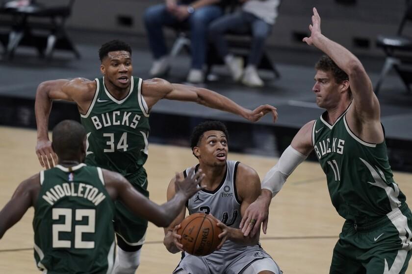 San Antonio Spurs forward Keldon Johnson (3) looks to score against Milwaukee Bucks defenders Khris Middleton (22), Giannis Antetokounmpo (34) and Brook Lopez (11) during the second half of an NBA basketball game in San Antonio, Monday, May 10, 2021. (AP Photo/Eric Gay)