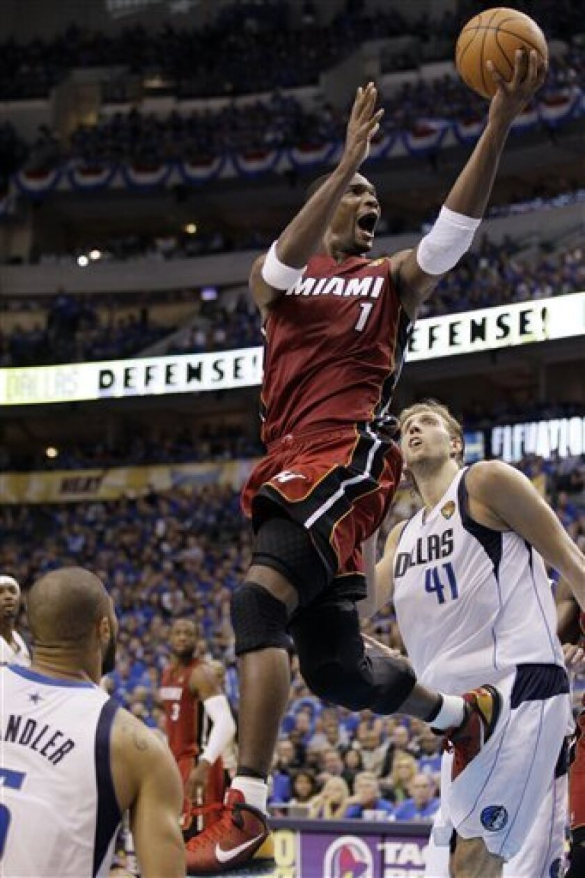 Miami Heat's Chris Bosh (1) shoots over Dallas Mavericks' Dirk Nowitzki during the first half of Game 3 of the NBA Finals basketball game Sunday, June 5, 2011, in Dallas. (AP Photo/Mark Humphrey)