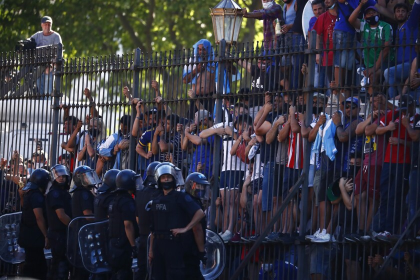 Mourning fans climb the fence of the presidential palace to get a glimpse of the casket carrying Diego Maradona's body.