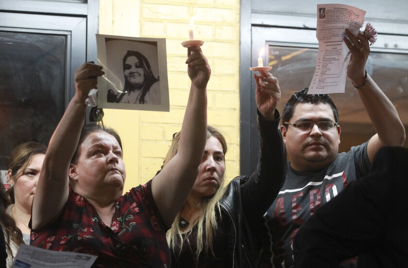 Ramón Mendoza, husband of Maribel Ibañez, who was shot and killed Wednesday night while working at a Church's Chicken restaurant, stands with his wife's sister, Gaby Merino, and mother, Emma Merino, during a vigil Friday night for Ibañez at the Church's Chicken restaurant where she was killed.
