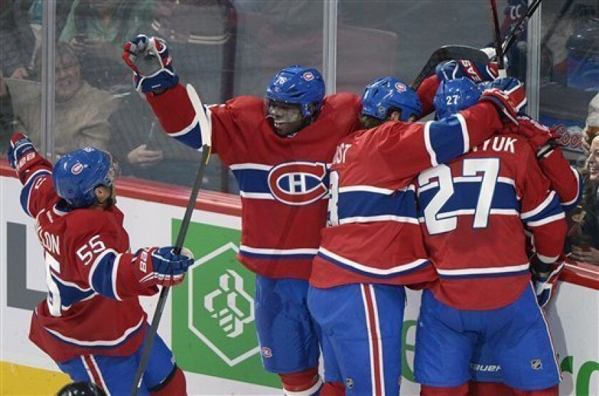 Montreal Canadiens' PK Subban (76), Francis Bouillon (55), Brandon Prust (8), and Alex Galchenyuk (27) celebrate a goal by teammate Brendan Gallagher, hidden, during the second period of  an NHL hockey game against the Buffalo Sabres in Montreal, Saturday ,Feb. 2, 2013. (AP Photo/The Canadian Press