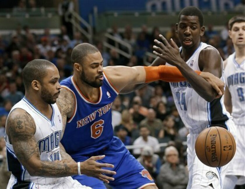Orlando Magic guard Jameer Nelson, left, and forward Andrew Nicholson, right, vie for a loose ball with New York Knicks center Tyson Chandler (6) during the first half of an NBA basketball game, Saturday, Jan. 5, 2013, in Orlando, Fla. (AP Photo/John Raoux)