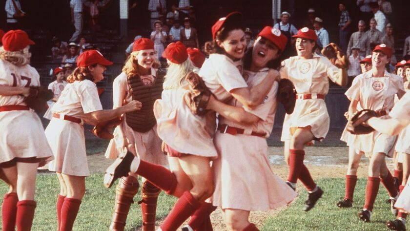 """Madonna, center left, and Rosie O'Donnell embrace in """"A League of Their Own"""" as Geena Davis, in catcher's gear, looks on."""