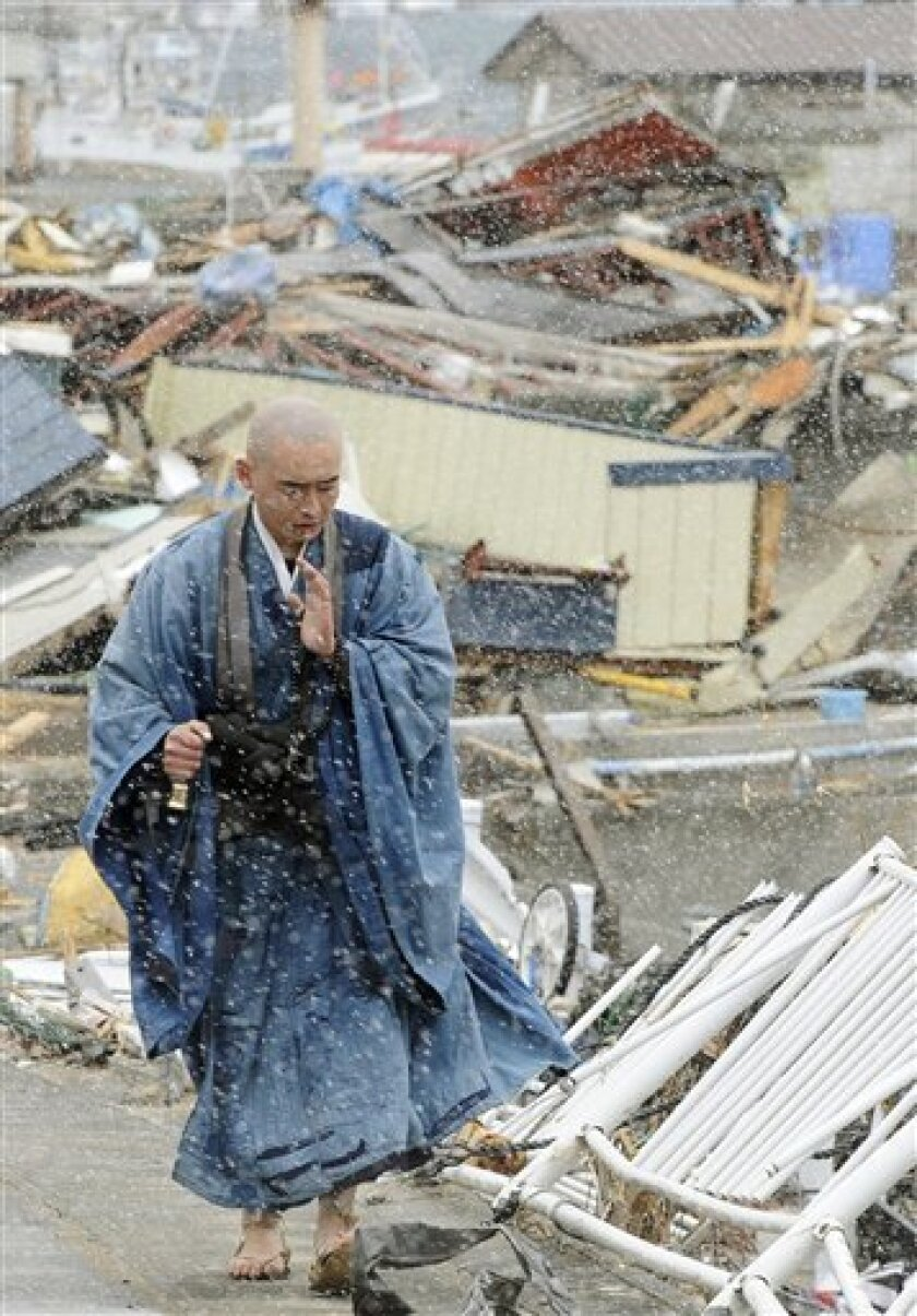 A Buddhist monk, offering prayer, walks through the area destroyed by a tsunami in Yamada, Iwate prefecture, northern Japan Monday, April 4, 2011. (AP Photo/Kyodo News) JAPAN OUT, MANDATORY CREDIT, NO LICENSING IN CHINA, HONG KONG, JAPAN, SOUTH KOREA AND FRANCE