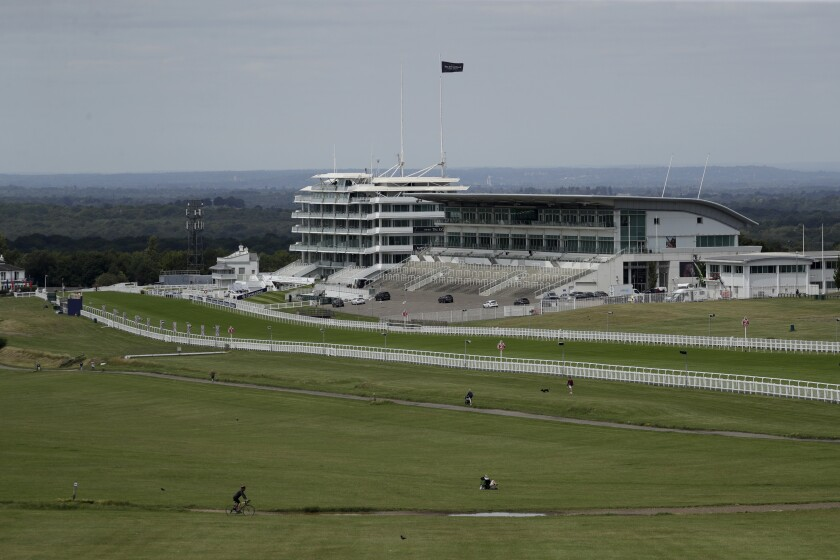 People cycle, walk and sit on the Downs surrounded by the Epsom Downs Racecourse, in Epsom, England, Friday, July 3, 2020. The Derby annual horse race will take place at the Epsom Downs Racecourse behind closed doors on Saturday amid the coronavirus pandemic. (AP Photo/Matt Dunham)