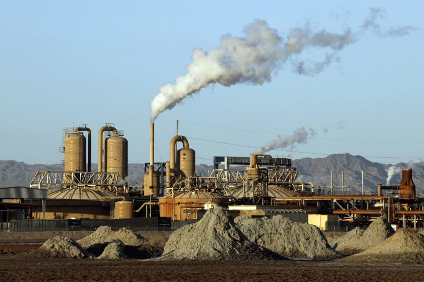 Plumes rise from smokestacks at a geothermal plant in the desert
