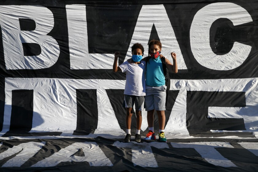 Khai Rieara, 10, left, and brother Keanu Rieara, 12, stand on Black Lives Matter banner near White House.