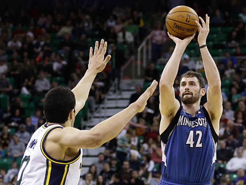 Minnesota's Kevin Love shoots over Utah's Enes Kanter on his way to his first career triple-double Saturday in Salt Lake City. (AP Photo/Rick Bowmer