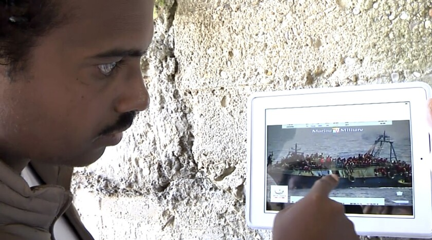 Mohammed Ali, from Sudan, points to his location in an Italian navy video showing the capsizing of a smuggler's boat.