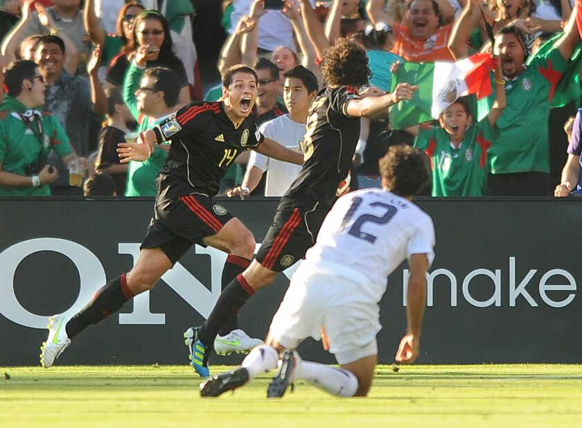 Skalij, Wally –– B581362974Z.1 PASADENA, CALIFONRIA JUNE 24, 2011–Mexico's Javier Hernandez, left, celebrates with goal scorer Andres Guardado in fron of USA's Jonathan Bornstein to tie the game in the 1st half of the Gold Cup Final at the Rose Bowl Saturday. (Wally Skalij/Los Angeles Times)