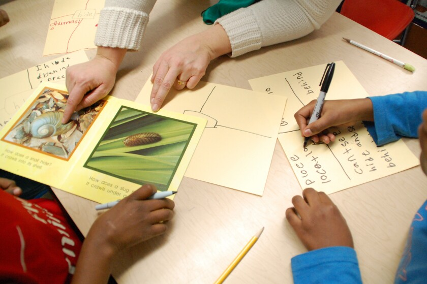 A teacher's hands pointing at pictures on a table, and two students writing or holding pens.