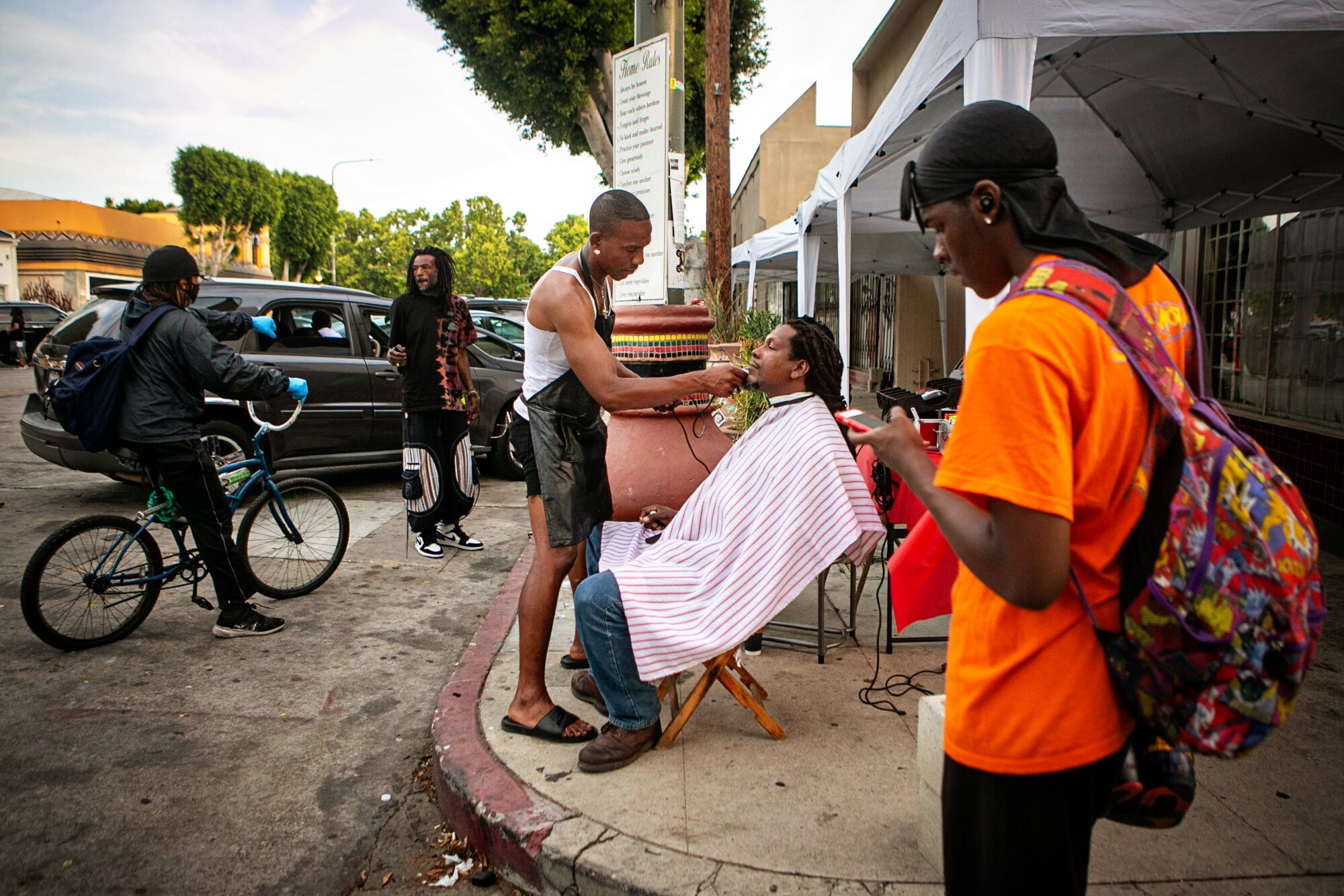 A man in a black apron gives a seated man a trim