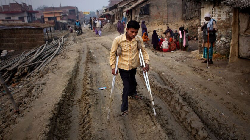 In this 2011 file photo, an unidentified man with polio walks on crutches in the village of Kosi, ar