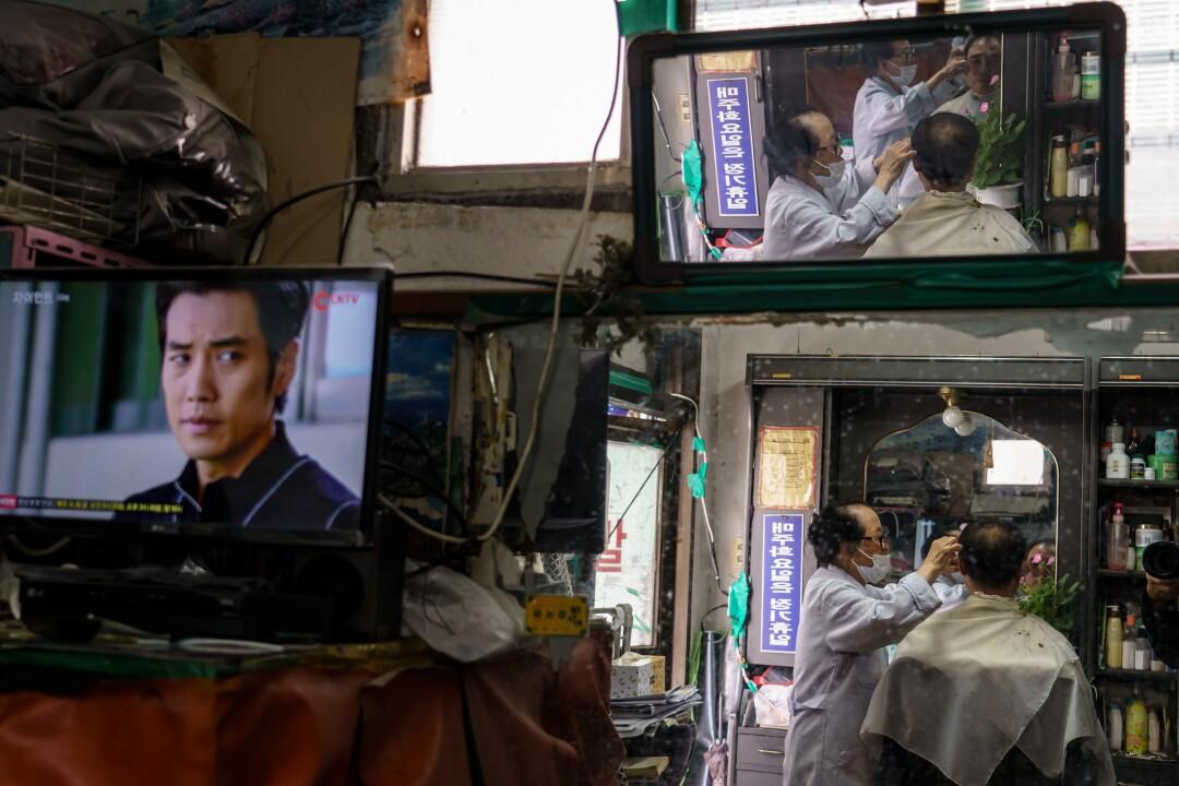 South Korean barber Lee Duk-hoon trims a customer's hair in Seoul