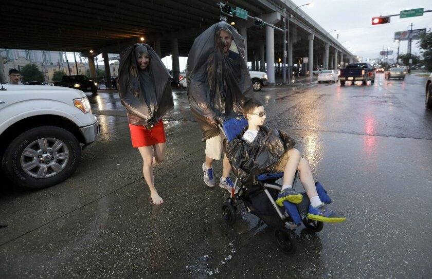 Houston Astros fans make their way across the street as they leave the stadium while rain falls after the Astros beat the Chicago White Sox 4-3 in a baseball game Saturday, May 30, 2015, in Houston. Heavy afternoon storms rolled through the Houston area. (AP Photo/David J. Phillip)