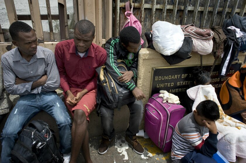 Three migrants wait to present themselves Thursday to U.S. authorities at the San Ysidro Port of Entry, part of a recent surge that has included a significant number of Haitians. These men said they were from the Congo and Guinea, and hoped to seek asylum.