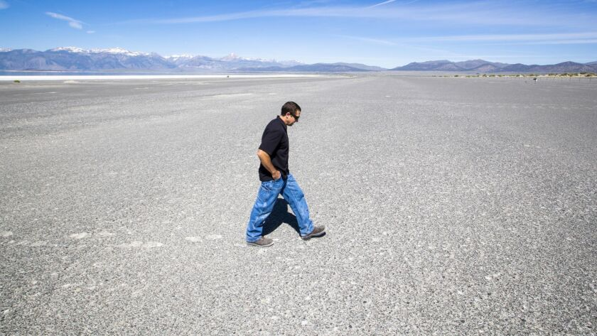 Phillip Kiddoo, air pollution control officer for the Great Basin Unified Air Pollution Control District, walks across salt and fine white sand at Mono Lake's shoreline, which is prone to dust storms.