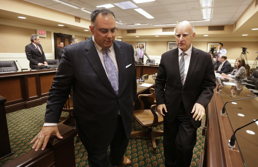 Former Assembly Speaker John Pérez (D-Los Angeles), left, and Gov. Jerry Brown leave a Assembly committee hearing last April. Brown signed a bill by Pérez on Tuesday with gives online consumers some new protections when they express opinions online.