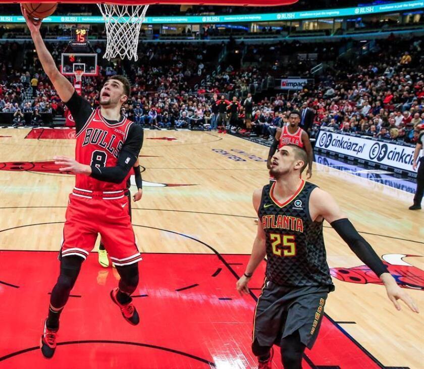 En la imagen, el jugador Zach LaVine (izq) de los Bulls de Chicago tira a canasta ante la defensa de Alex Len (dcha), de los Hawks de Atlanta. EFE/Archivo