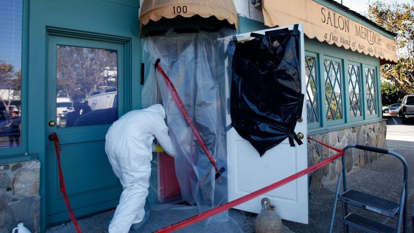 Crime scene workers use protective suits as they enter the scene of a mass– shooting at Salon Meritage in Seal Beach on Oct. 13, 2011.