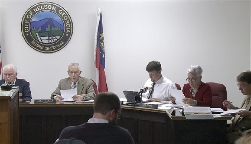 In a photo made from video the Nelson, Ga. City Council meets to vote on a mandatory gun ownership ordinance for all heads-of-household, Monday, April 1, 2013, in Nelson Ga. Left to right: Council member Jackie Jarrett, Mayor Mike Haviland, council member Duane Cronic, council member Edith Portillo, city attorney Jeff Rusbridge. The ordinance in the city of Nelson _ population 1,300 _ was approved Monday night and goes into effect in 10 days. However, it contains no penalties and exempts anyone