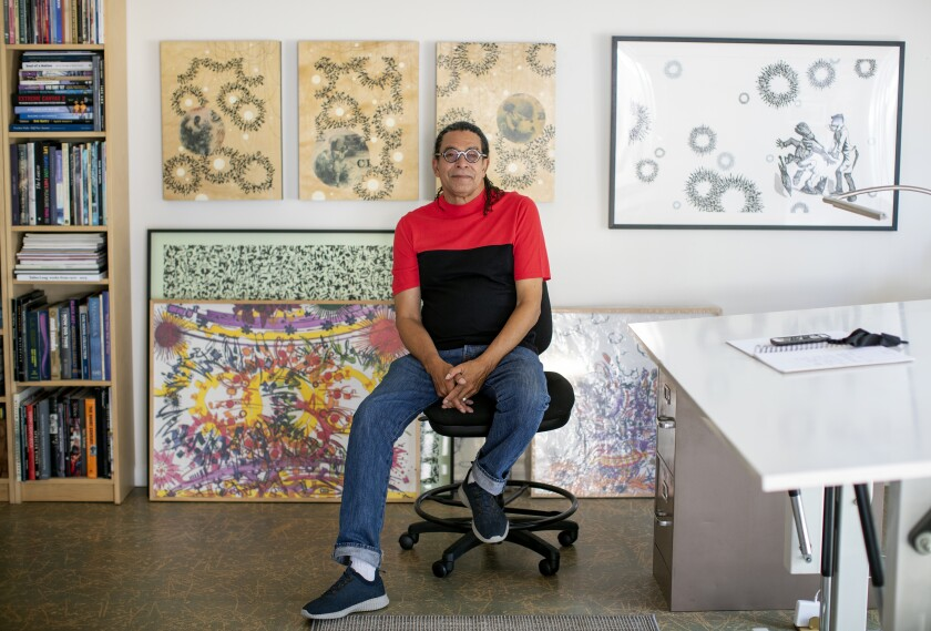 Mark Steven Greenfield sits in a chair in his studio, surrounded by paintings on the wall and stacked on the floor