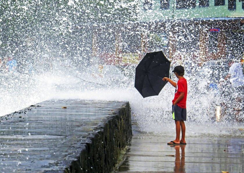 A boy holds an umbrella to a wave in Kailua-Kona on the island of Hawaii, Friday, Aug. 8, 2014. Iselle, the first tropical storm to hit the state in 22 years, knocked out power, caused flooding and downed trees when it crossed onto the Big Island in a rural and sparsely populated region. (AP Photo/Chris Stewart)