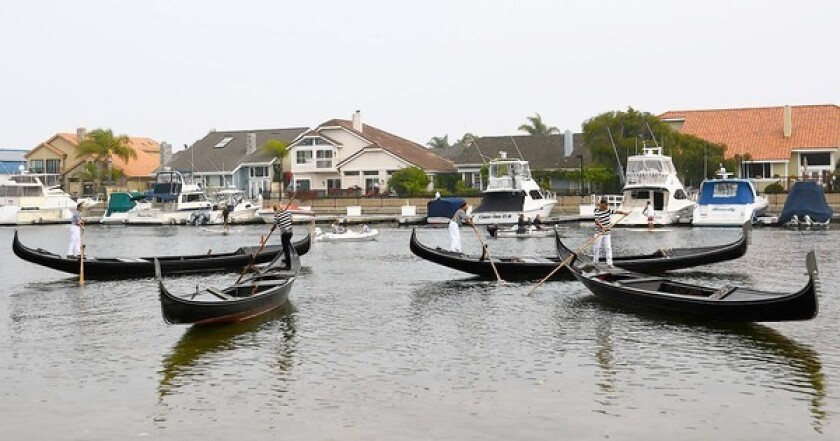 """Gondola racers Parker Harrison of Newport Beach, Richard """"Ricardo"""" Cordaley of Sunset Beach, Marcello of Rhode Island, and Giovanni of Minnesota gather their boats before the 2013 U.S. Gondola Nationals in Huntington Harbour on Saturday."""