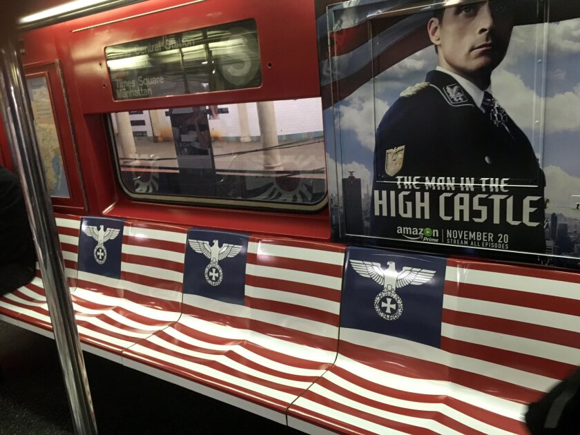 """This Nov. 23, 2015 photo provided by Ann Toback shows a poster and other Nazi-themed imagery in a New York City subway car. On Wednesday, Nov. 25, New York Gov. Andrew Cuomo ordered the campaign promoting the Amazon video series called """"The Man in the High Castle"""" removed from the New York City subway system, as other public officials including Mayor Bill de Blasio condemned them. (Ann Toback via AP) MANDATORY CREDIT"""