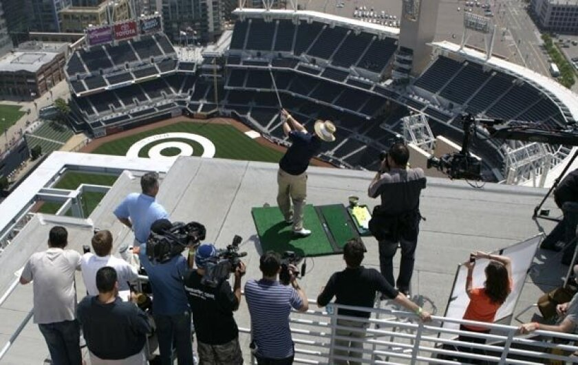 PGA golfer Briny Baird hits one of 10 golf balls from the roof of the Omni Hotel downtown into Petco Park on Monday as part of a restaurant promotion. Accompanied by Padres GM Kevin Towers, who also launched a couple of balls, the two aimed for a 20-yard-wide bull's-eye 34 floors below. (Nancee E.