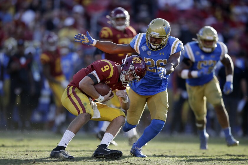 USC quarterback Kedon Slovis (9) is tackled by UCLA linebacker Leni Toailoa.