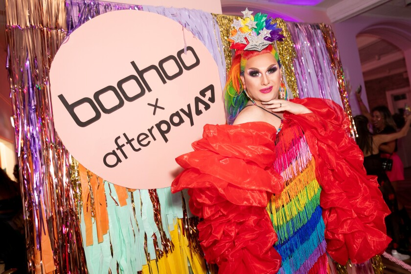 A colorfully dressed young woman stands in front of a sign that say Boohoo x Afterpay