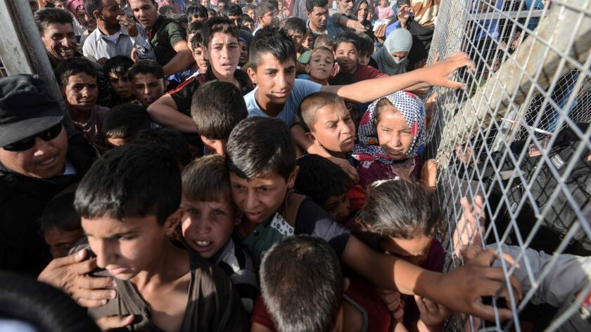 Iraqis line up behind a fence at the Hassan Sham camp for internally displaced people, 20 miles east