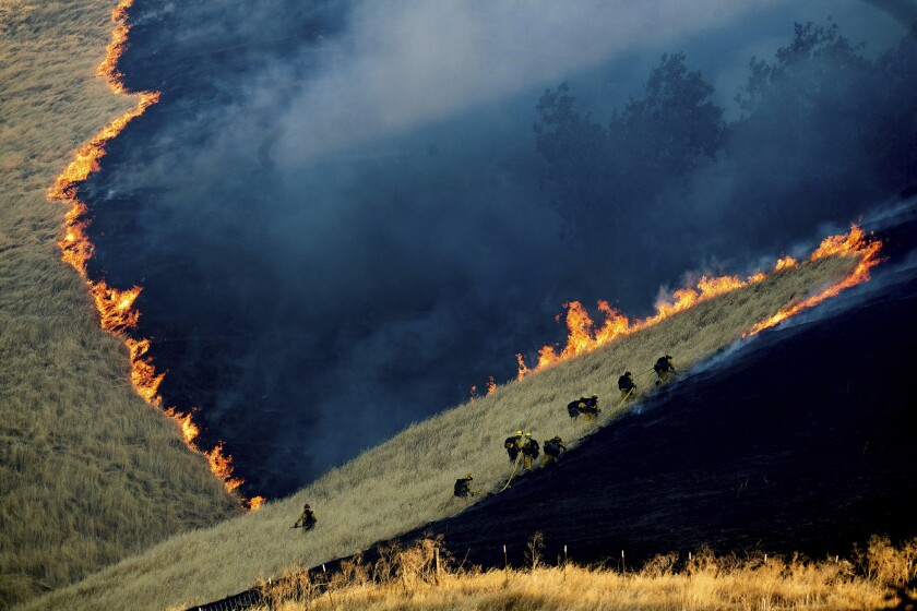 FILE - In this Aug. 3, 2019, file photo, firefighters battle the Marsh Fire near the town of Brentwood in Contra Costa County, Calif. California fire officials say acreage burned so far in 2019 is down 90% compared to the average over the past five years. (AP Photo/Noah Berger, File)