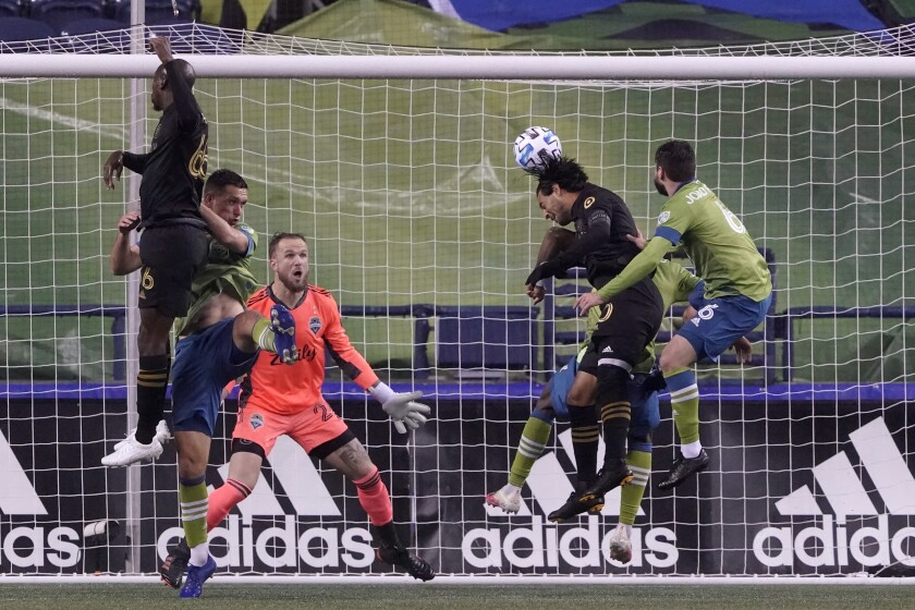 LAFC's Carlos Vela heads the ball in front of Seattle Sounders goalkeeper Stefan Frei.
