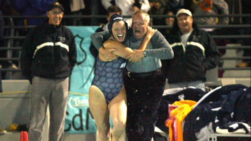 Newport Harbor head coach Bill Barnett leaps into the pool with player Lauren Jarvey as they win the
