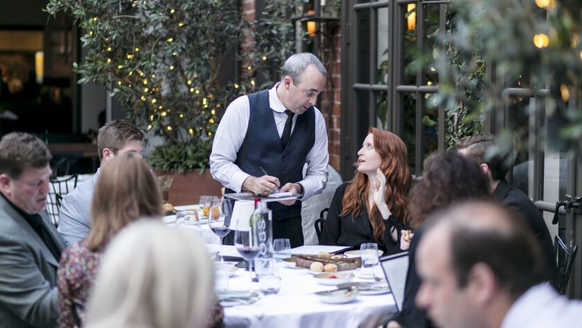 BEVERLY HILLS, CALIFORNIA - June 19, 2019: Evening service gets underway at Spago's shaded, green p